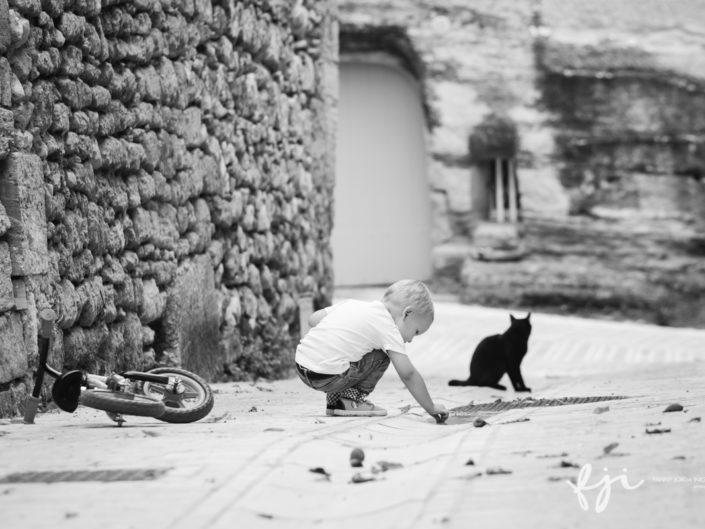 Petit garçon et chat noir dans la rue